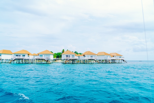 Tropical maldives resort hotel and island with beach and beautiful sky