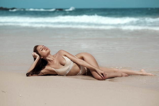 A tropical model with freckles on her face and wearing beige bikini relaxing on the sea