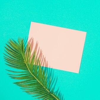 鮮やかなブルーにピンクの紙カードノートが付いた熱帯のモンステラの葉。最小限の夏の構成。