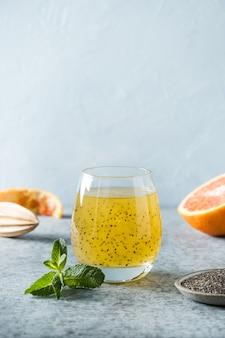 チアシードとガラスのトロピカルオレンジジュース。閉じる。垂直フォーマット。