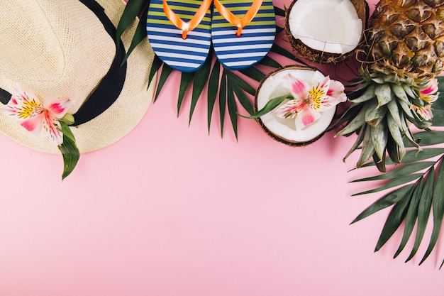 Tropical palm leaves, hat, slippers, pineapple, coconut on white background.