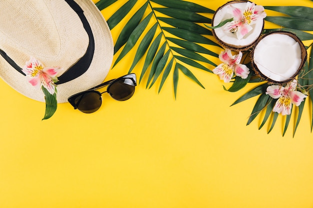 Tropical palm leaves, hat, sunglasses, coconut on yellow background.