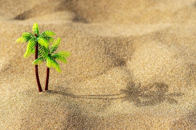 砂の上の熱帯のヤシのおもちゃ