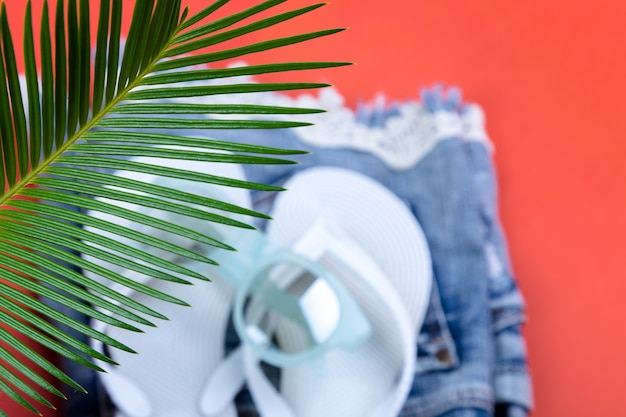 Ветви тропических пальм с размытым набором женских вещей, аксессуаров для пляжного сезона
