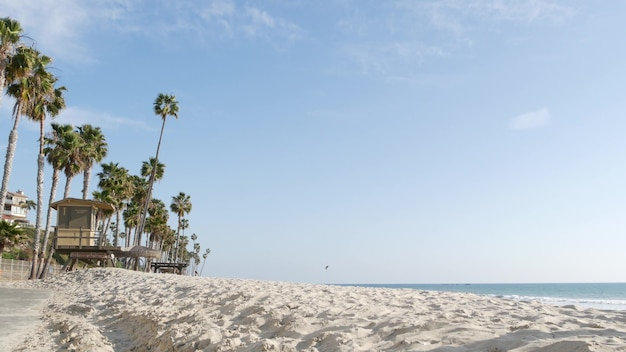 Tropical palm trees, white sandy beach by sea water wave, pacific ocean coast, san clemente california usa. blue sky and lifeguard tower. life guard watchtower hut, summertime shore. los angeles vibes