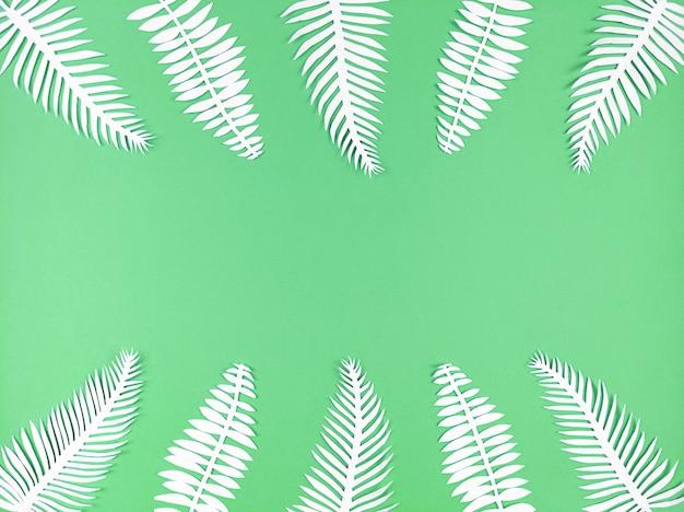 トロピカルペーパーは緑の背景に残し、コピースペースで平らに横たわっています。