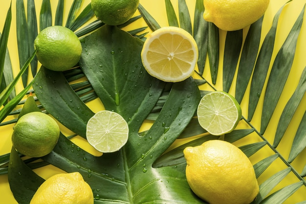 Tropical pattern of fruits, banana, lime, leaves palms on yellow. top view. summer vacation. detox tour.