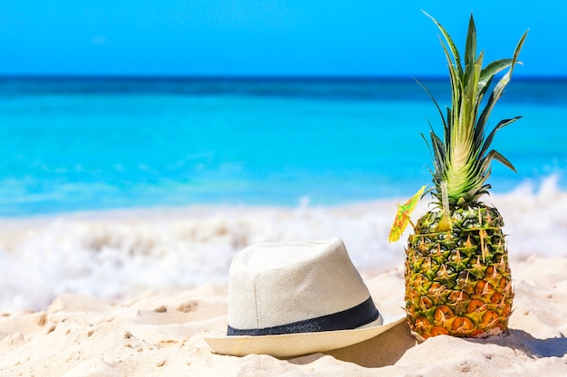 Тропический ананасовый коктейль пина колада в шляпе на карибском пляже