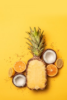 Tropical pineapple, oranges, lemon and coconut on a pastel background.