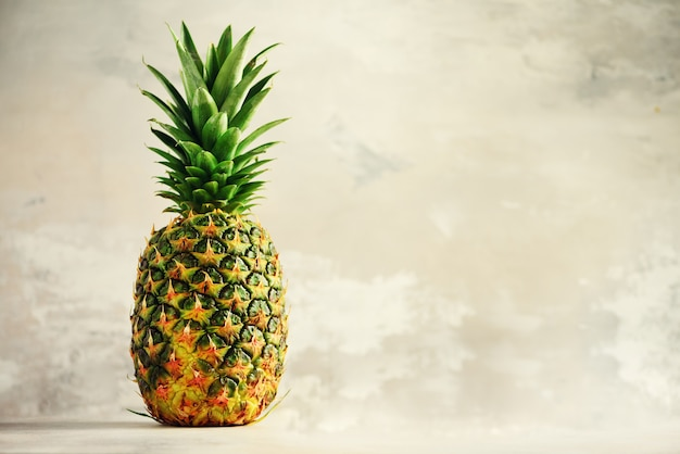 Tropical pineapples on gray background. summer, holiday concept. raw, vegan, vegetarian, clean eating diet