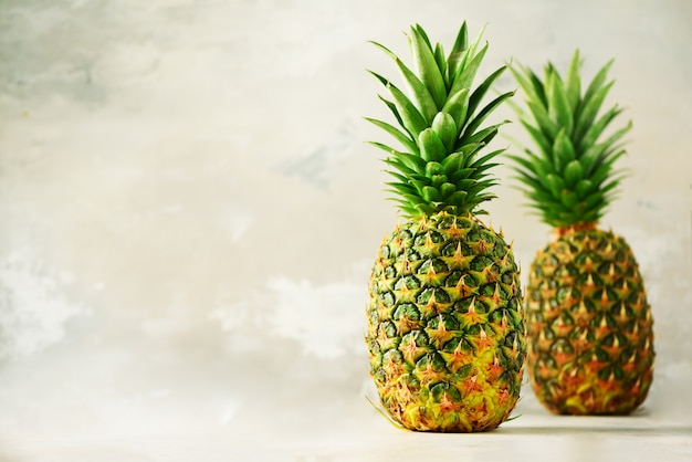 Tropical pineapples on gray background. summer, holiday concept. raw, vegan, vegetarian, clean eating diet.