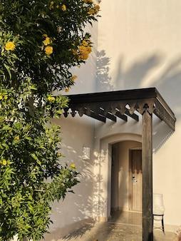 家の建物のベージュの壁に黄色い花と熱帯植物