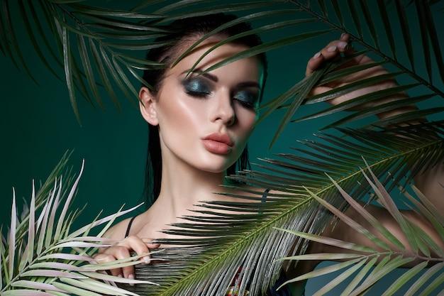 잎 야자수에서 열 대 초상화 섹시 한 여자입니다. 밝은 녹색 화장, 야자수의 그림자가 소녀의 얼굴에 남습니다. 아름다운 메이크업