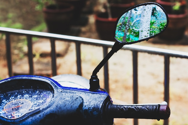 Tropical rain. mirror of motorbike.