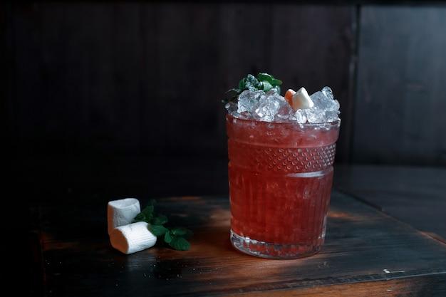 실내 빈티지 나무 테이블에 신선한 주스, 과일 시럽, 민트, 얼음, 과일 조각이 추가 된 열대 레드 알콜 칵테일. 좋은 주말. 알코올 시음