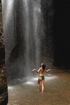 열대의 휴식. 하늘을 올려다보며 팔을 벌리고 있는 행복한 젊은 여성