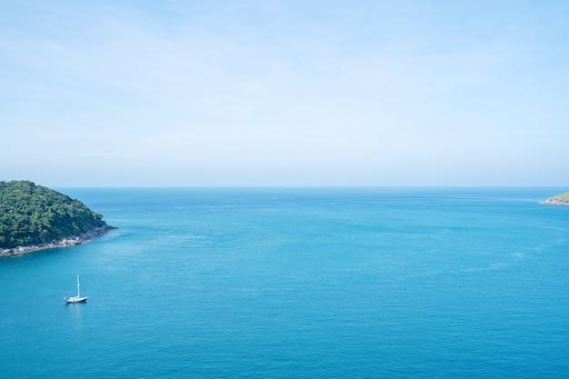 수평선에 작은 섬과 하얀 솜털 구름 바다 표면에 물결이 일고 잔잔한 열대 바다