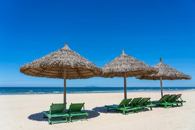 푸른 하늘과 짚 우산 열 대 모래 해변과 여름 바다 물. 여행과 자연 개념