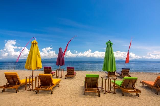 열대 모래 해변. 빈 갑판 의자, 닫힌 비치 파라솔과 구름과 푸른 하늘