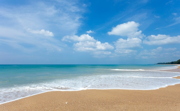 Tropical sandy beach with blue ocean and blue sky background