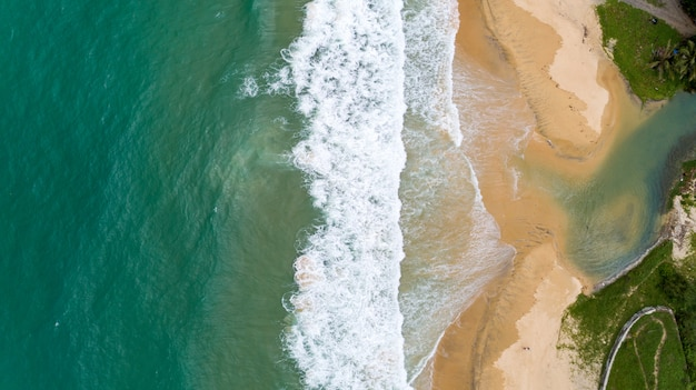 Tropical sea and wave crashing on sandy shore at karon beach in phuket thailand aerial view drone camera top down.