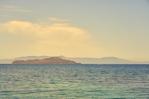 地平線の霧の中に岩の島々を背景にした熱帯の海。スペースをコピーします。