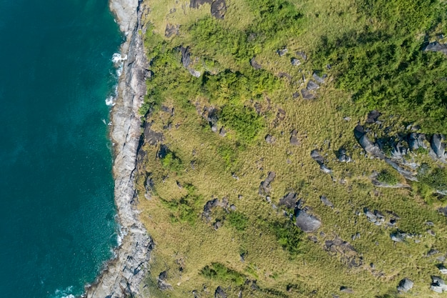 Tropical sea with wave crashing on seashore and mountain aerial view drone top down view