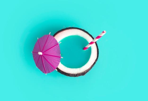 熱帯の夏と休暇の最小限の概念。カクテルストローと青い背景の上のココナッツ。休暇、旅行、ビーチのアイデア。
