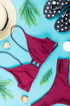 Tropical summer concept with red bikini, leaves and seashells on blue