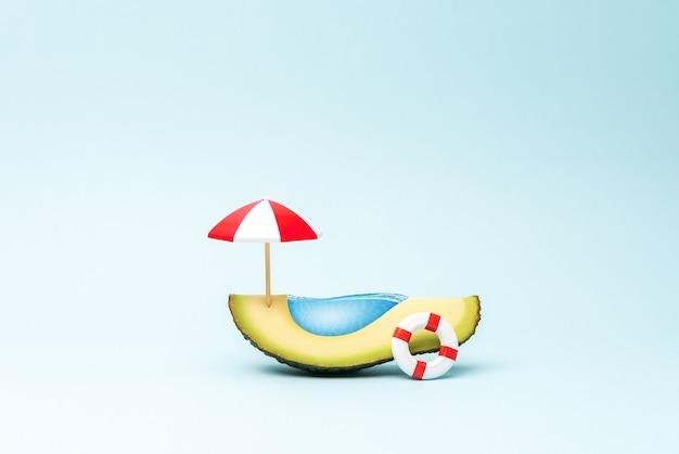 Концепция тропического бассейна с зонтиком от солнца из фруктов авокадо и плавательным кольцом