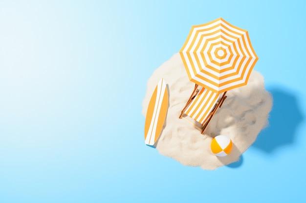 열대 휴가 배경. 모래 섬에서 활동적인 휴식을 위해 우산과 해변 액세서리가 달린 일광욕 의자, 복사 공간, 평면도