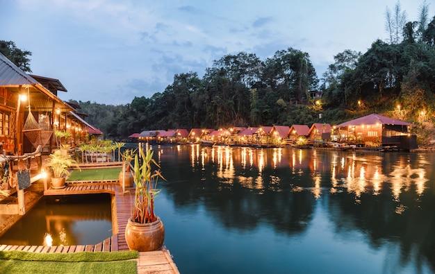 Tropical wooden raft resort illumination on river kwai at dawn