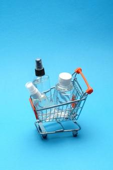 Концепция гигиены предохранения от вируса короны - жидкость дезинфицирующего средства руки спирта в troplley магазинной тележкаи на голубой предпосылке. , ручная стирка в корзине