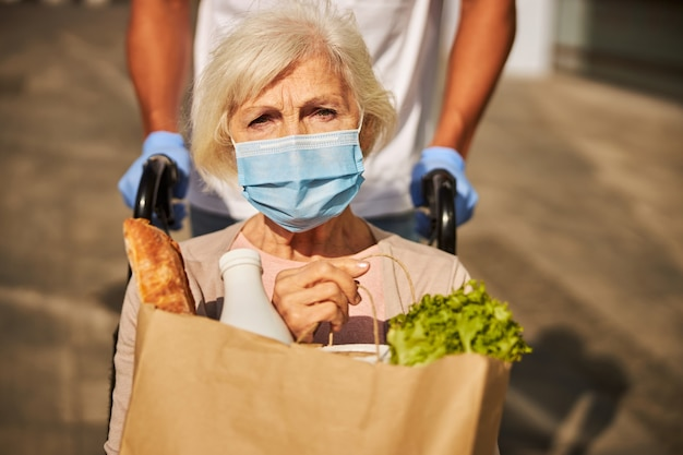 Troubled aging person with a face mask keeping a brown bag with baguette, milk and lettuce