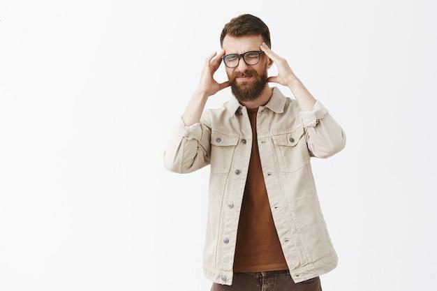 Обеспокоенный и измученный бородатый мужчина в очках позирует на фоне белой стены