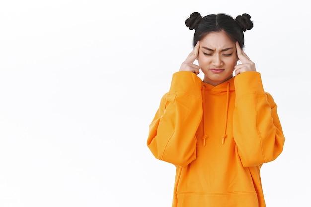 편두통을 앓고 있는 곤란하고 불안한 귀여운 아시아 소녀, 하루 종일 공부로 인한 두통, 찡그린 표정으로 고통을 느끼고 사원을 마사지하고, 눈을 감고 집중을 시도하고, 흰 벽에 서 있습니다.