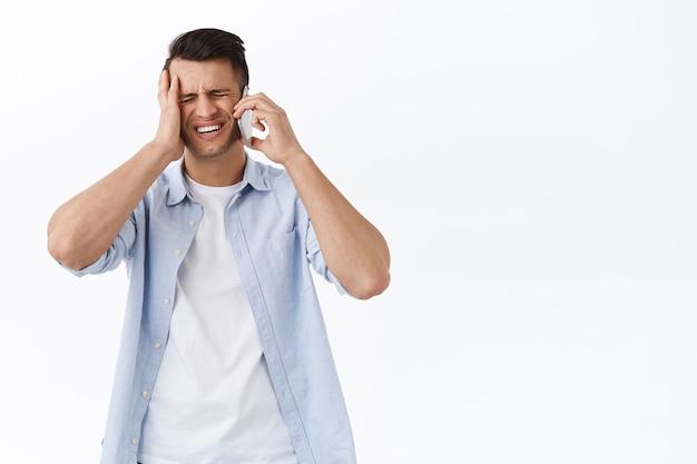 困惑して動揺したハンサムな男は、約束を忘れ、欲求不満のタッチヘッドに顔をゆがめ、人と電話で会話し、携帯電話での重要なタスクを思い出しました