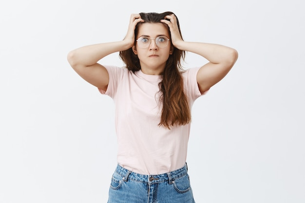 Troubled anxious young brunette with glasses posing