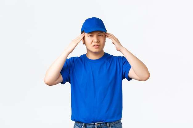 青い帽子とtシャツで問題を抱えたアジアの宅配便はめまいがするか過労に見えます。配達人は圧力を処理できない、頭に触れる、頭痛や倦怠感を感じる、白い背景に立っている