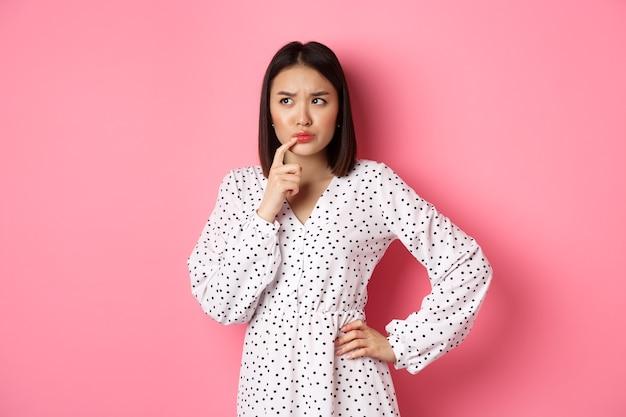 고민하는 아시아 소녀 결정, 인상을 찌푸리고 생각하면서 입술을 만지고, 왼쪽 상단 모서리에서 확실하지 않고 선택하고, 분홍색 위에 서 있습니다.