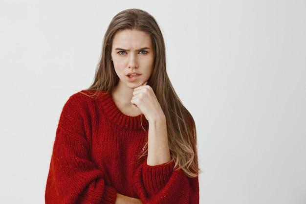 時間内にプロジェクトを終了しようとする問題のある魅力的なフリーランサー。スタイリッシュなルーズセーター、眉をひそめ、唇をかむ、あごに手を握って、真剣に考えて心配している魅力的なヨーロッパの女性