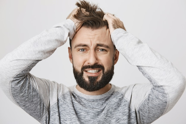 Troubled bearded guy in panic tossing hair and look scared