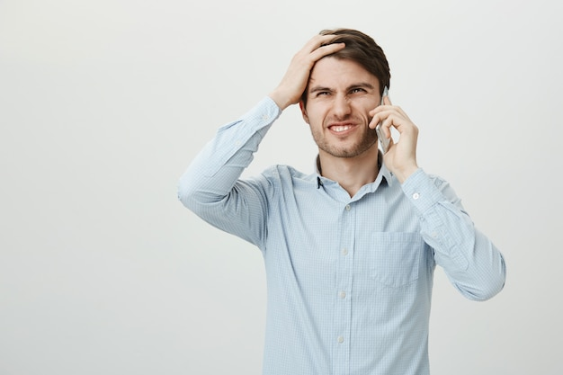 Troubled businessman talking phone, facepalm disappointed