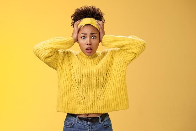 問題を抱えた心配している困惑した女性のアフリカ系アメリカ人の従業員の義務は複雑に見えますパニックホールド手頭を広げて目を広げますショックを受けた顔のトラブル神経質に考えて不安なカメラ、黄色の背景を見てください。