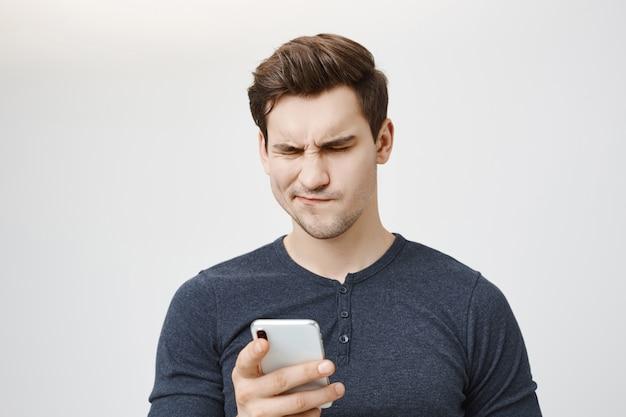 Обеспокоенный сбитый с толку парень, глядя на сообщение мобильного телефона