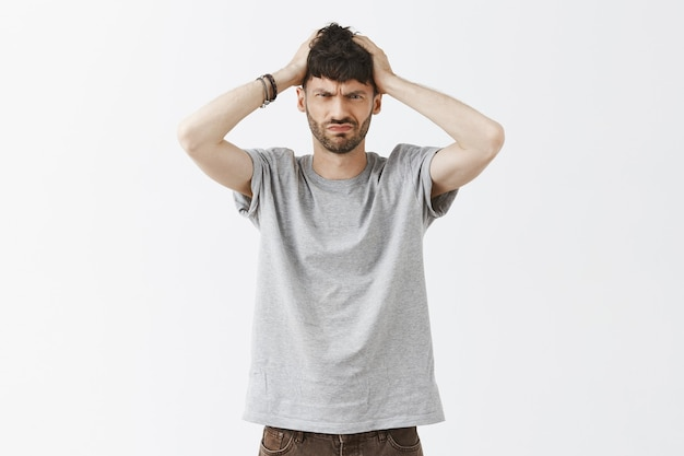 Troubled and confused handsome guy posing against the white wall