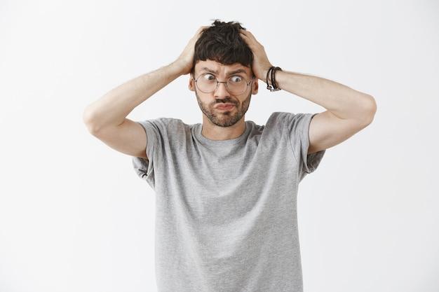 Bel ragazzo turbato e confuso in posa contro il muro bianco