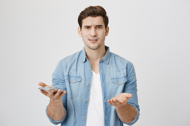 Troubled and confused man shrugging as holding mobile phone