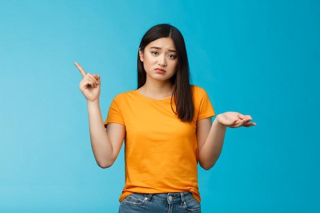 Обеспокоенная милая расстроенная азиатская девушка не может попросить вашу помощь, указывая в левый верхний угол, неуверенно пожимая плечами, выглядит расстроенным и грустным, сомнительный ответ, не может справиться с проблемой, стоять на синем фоне