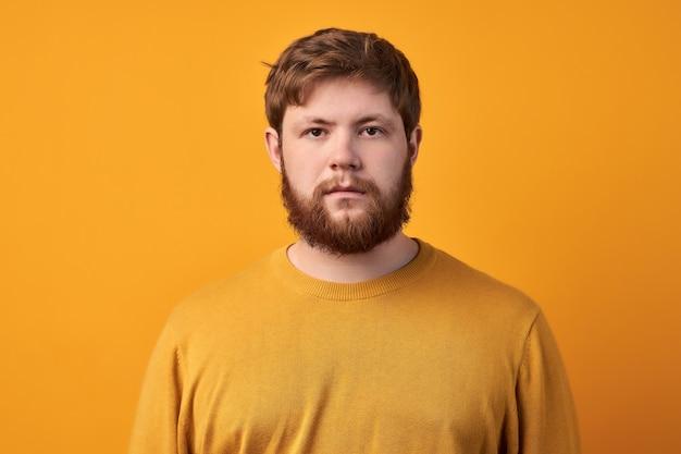 Обеспокоенный, недовольный бородатый мужчина хмурится, чувствует себя грустным, расстроенным и расстроенным, ему скучно сидеть на карантине, он недоволен упущенным шансом, небрежно одет, изолирован на желтом фоне
